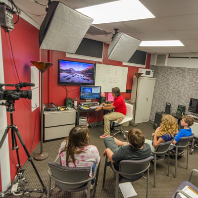 Staff teaching teens how to edit video at TASCO Center for Teen Technology